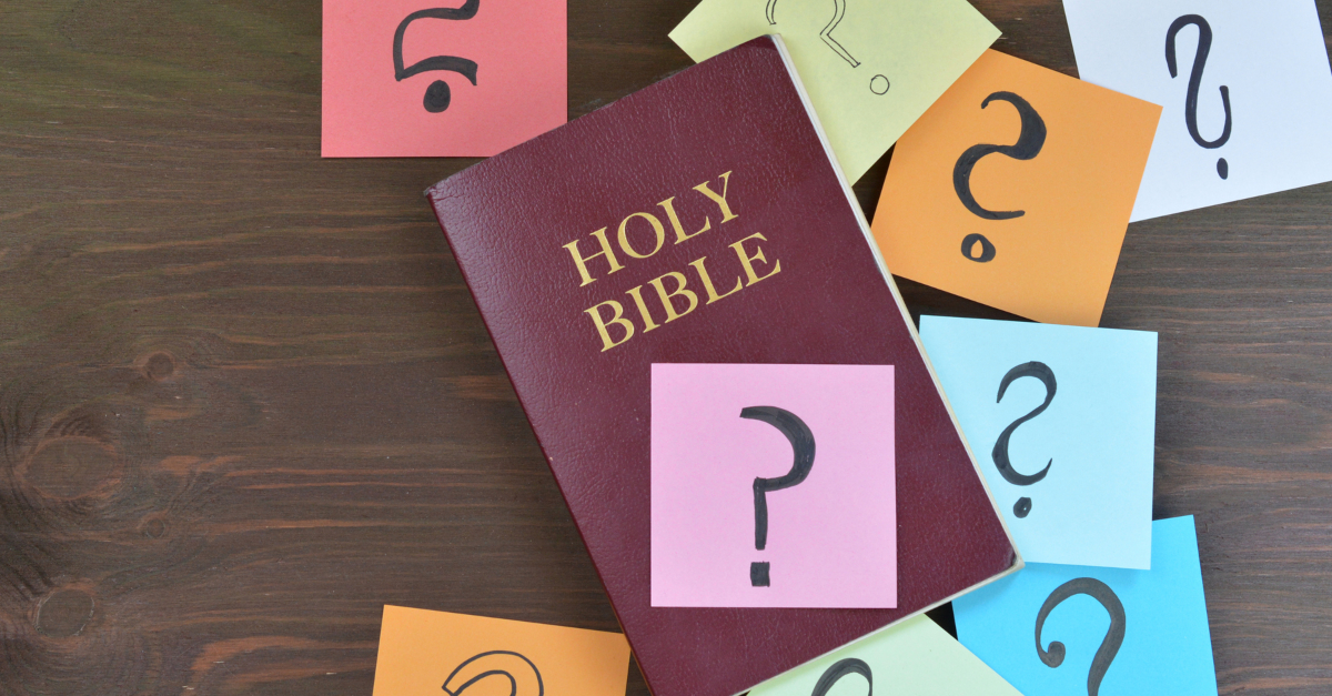 bible covered with post-it notes with question marks on them
