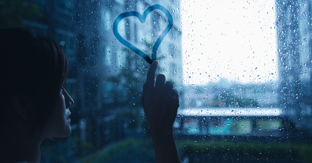 woman tracing heart on window on rainy day, how to find relief when hurting