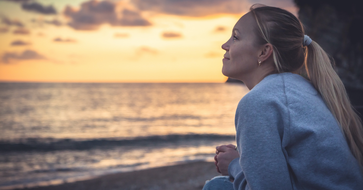 woman looking peaceful at sunrise ocean, what to do when make mistake